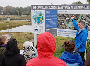 "Mecklenburg County Storm Water Engineering & Flood Mitigation Program Manager Tim Trautman explains the county's buyout program to students in CRC Director Gavin Smith's ""Natural Hazards and Climate Change"" course during a trip to Charlotte on Nov. 9, 2018. Trautman explained the process by which half of an apartment complex east of downtown Charlotte was bought out and converted to a public park in the floodplain, increasing the value of some nearby homes."